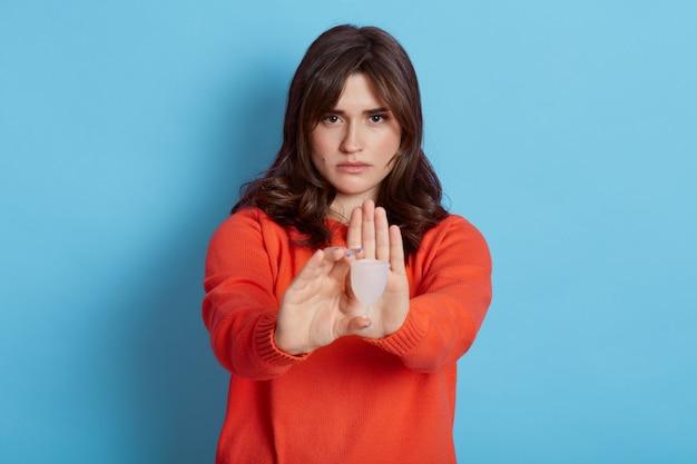 プラスチック製の月経カップを手に持って、手のひらで停止ジェスチャーを示しているブルネットの女性の水平方向のショット