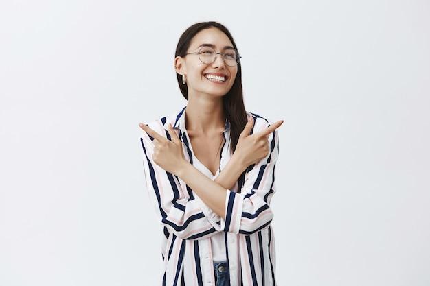 眼鏡とストライプのブラウスでのんきな社交的でフレンドリーなスタイリッシュな女性の水平方向のショット、手を交差させ、さまざまな側面を指して、楽しい幸せな笑顔で右を見て
