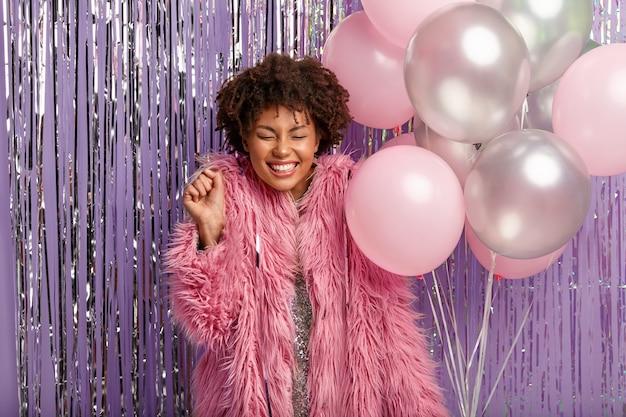 Горизонтальный снимок жизнерадостной афро-леди сжимает кулак, наслаждается празднованием, одетая в стильный костюм и держит воздушные шары