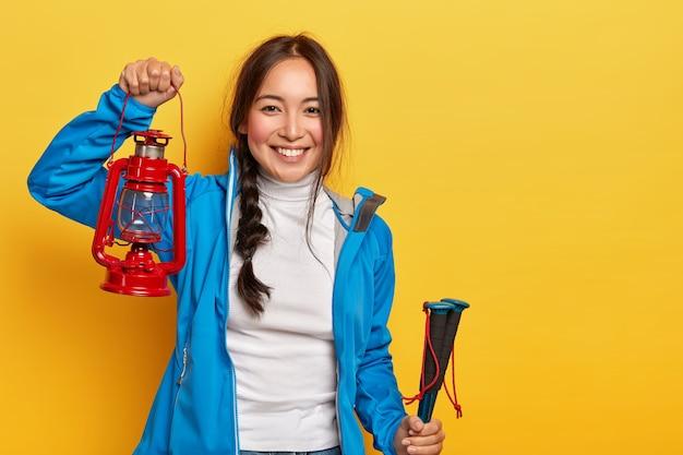 어두운 엮과 쾌활한 아시아 여자의 가로 샷, 가스 램프를 보유하고 활성 마모를 입은 트레킹 스틱, 긍정적 인 미소가 노란색 벽 위에 서있다.