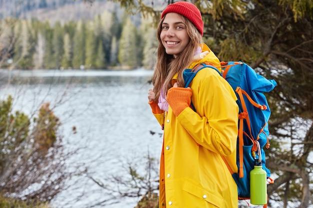 陽気な白人女性放浪者の水平方向のショットは、カメラに横に立って、美しい自然を楽しんでいます