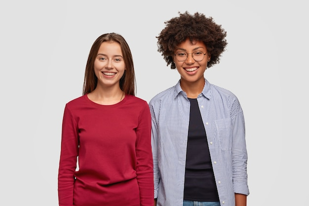 Горизонтальный снимок веселых многонациональных молодых женщин с довольными выражениями лиц