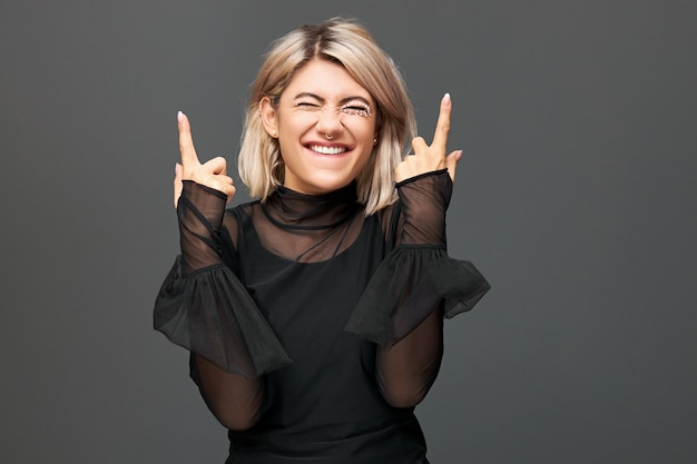 좋은 긍정적 인 뉴스를 즐기고, 기쁨을 표현하고, 검지 손가락을 가리키며, 성공을 축하하는 세련된 투명 드레스를 입고 쾌활한 기뻐 황홀한 젊은 유럽 여성의 가로 샷