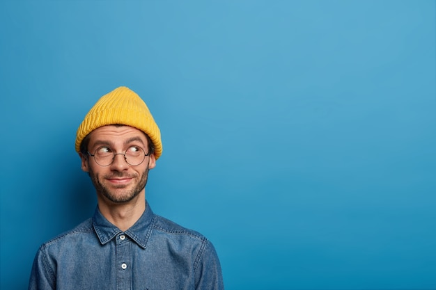 쾌활한 만족스러운 남자의 가로 샷은 꿈꾸는 만족스러운 표정으로 보이고 세련된 옷을 입고 무언가를 할 의도가 있습니다.