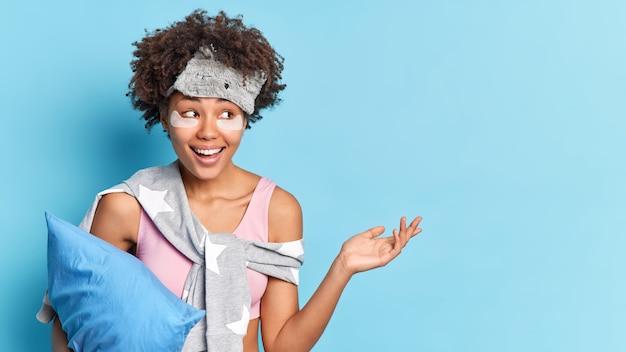 파자마와 수면 마스크를 입은 곱슬 머리를 가진 쾌활한 여자의 가로 샷은 긍정적으로 파란색 벽 빈 복사본 공간 옆으로 베개 포즈를 보유하고 손 미소를 제기