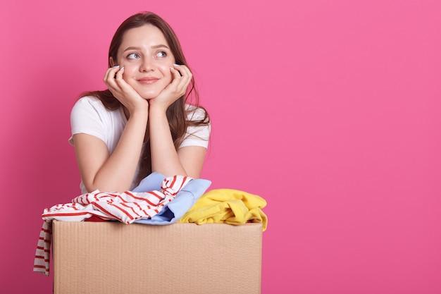 Горизонтальная съемка жизнерадостного молодого добровольного положения изолированного над румяным, представляя около коробки коробки полной подаренной одежды. улыбающиеся женщина смотрит в сторону, держать руки под подбородком.