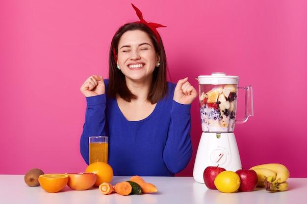 쾌활 한 젊은 여자의 가로 샷 믹서 기 스무디를 만든다. 굽은 팔꿈치와 닫힌 눈을 가진 아름다운 갈색 머리는 맛있는 과일 칵테일을 준비하는 동안 행복해 보입니다. 건강한 라이프 스타일 개념.