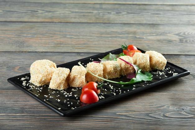Горизонтальный снимок сырных шариков с sezam, который подают на тарелке с помидорами черри и некоторыми зеленью, вкусными вкусными закусками, меню для гурманов, меню деликатесов, едой.