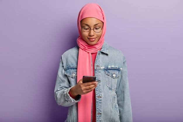 イスラム教の集中した喜びの暗い肌の女性の水平方向のショット、現代の携帯電話でメッセージを入力し、ヒジャーブとデニムのジャケットを着て、通知を読み、ワイヤレスインターネットをサーフィンします