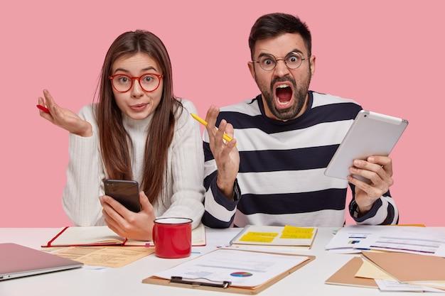 Горизонтальный снимок смущенной женщины и раздраженного мужчины обсуждают графики, работают над университетским проектом, используют современные технологии, вместе делают домашнее задание, изолированные на розовой стене. концепция молодежи и работы