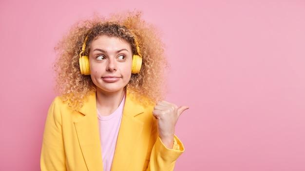 호기심 곱슬 머리 젊은 여자의 가로 샷 포인트 엄지 손가락 멀리 분홍색 벽 위에 절연 귀에 스테레오 헤드폰을 착용하는 공식적인 옷을 입고 복사 공간을 보여줍니다. 이 길을 따라