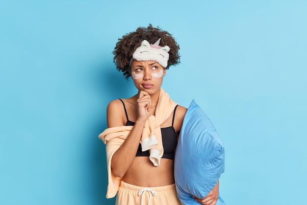Горизонтальный снимок кудрявой женщины, одетой в пижаму, отдыхающей дома, с коллагеновыми пластырями, держащей подушку, изолированной над синей стеной, в глубокой задумчивости