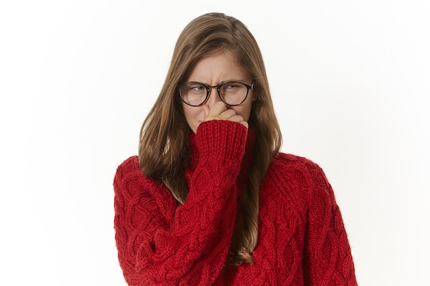 Горизонтальный снимок возмущенной и недовольной молодой женщины в очках и свитере, которая гримасничает и зажимает нос из-за неприятного запаха тела, тухлой пищи, грязных носков или вонючих потных подмышек