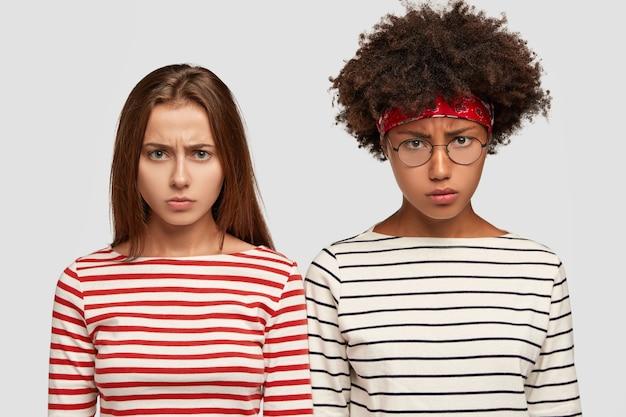 縞模様の服を着て、ネガティブな表情の不機嫌な女性の横向きのショットは、不機嫌そうな表情をしています