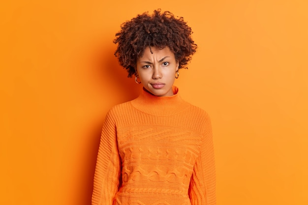 Горизонтальный снимок недовольной молодой афроамериканской женщины, хмурящейся, сердито смотрит в камеру