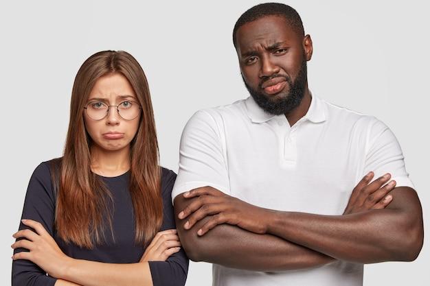 Горизонтальный снимок недовольной молодой многонациональной пары с жалкими взглядами