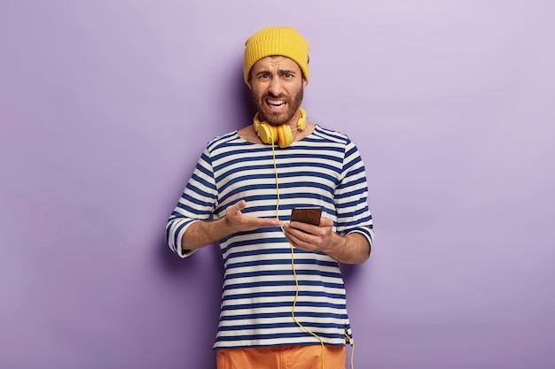 不満のある男性の横向きのショットがスマートフォンデバイスを指さし、不快な表情をし、スタイリッシュな服を着て、新しいアプリケーションの使い方を理解できません