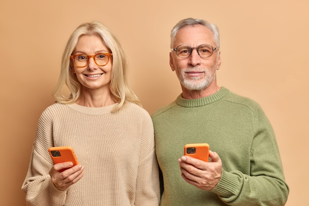 노인 부부의 수평 샷은 현대 기술을 사용하여 스마트 폰이 무선 인터넷에 연결된 문자 메시지를 읽고 갈색 벽 위에 절연 캐주얼 점퍼를 착용합니다.