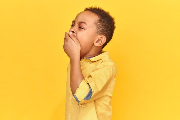 長い疲れた一日の後に疲れている手あくびで口を覆っている黄色いシャツを着ている疲れ果てた眠そうなアフリカの男子生徒の水平方向のショット。退屈、睡眠、就寝時間、寝具のコンセプト