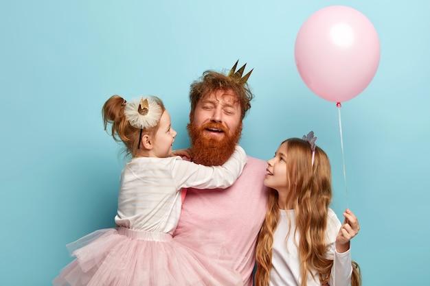 피로 젊은 수염 난된 남자의 수평 샷, 생강 머리, 아이들과 놀고 피곤. 두 딸은 다정한 아빠와 함께 휴가를 보내고 분홍색 풍선을 들고 있습니다. 축제의 날 개념