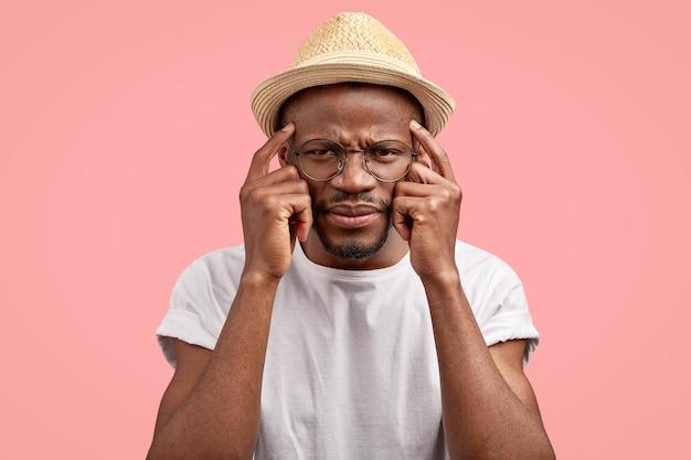 Горизонтальный снимок разочарованного темнокожего парня, который держит указательные пальцы на висках, с недовольным выражением лица.