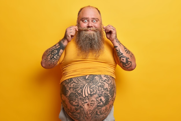 大きなおなか、腕と腹に入れ墨、黄色のtシャツを着た口ひげを回転させ、ビールをたくさん飲み、ジャンクフードを食べるように肥満を持っている面白い厚い男の水平方向のショット。 fatso怠惰な男性