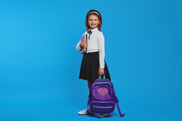 Горизонтальный снимок девушки в рюкзаке и школьной форме с книгами