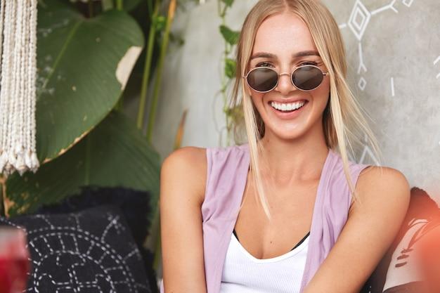 スタイリッシュな色合いのうれしそうな女性の水平ショットは、前向きで、快適なソファで再現し、元気いっぱいになり、夏の休暇を楽しみます。肯定的な感情、休息、ライフスタイルのコンセプト