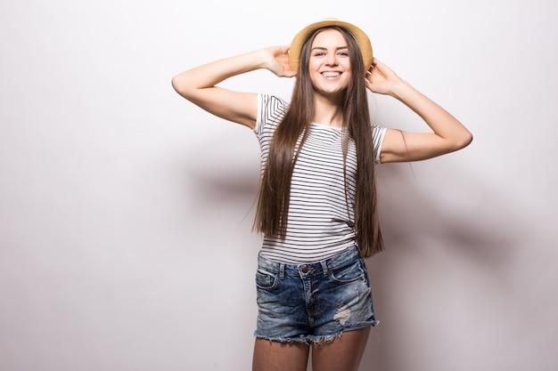 Горизонтальный снимок великолепной девушки-модели держит руку на соломенной шляпе, носит белый топ с открытыми плечами, выглядит уверенно, изолированно на белой стене
