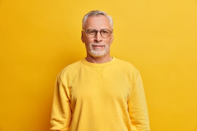 Горизонтальный снимок седого мужчины с морщинами в очках и повседневном желтом джемпере смотрит прямо вперед, удовлетворенное выражение лица позирует в помещении
