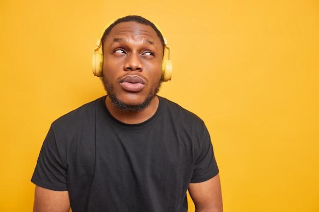 수염이 있는 잘생긴 성인 남성의 수평 샷은 수심에 찬 표정으로 위에 초점을 맞추고 무선 헤드폰을 통해 음악을 듣습니다.