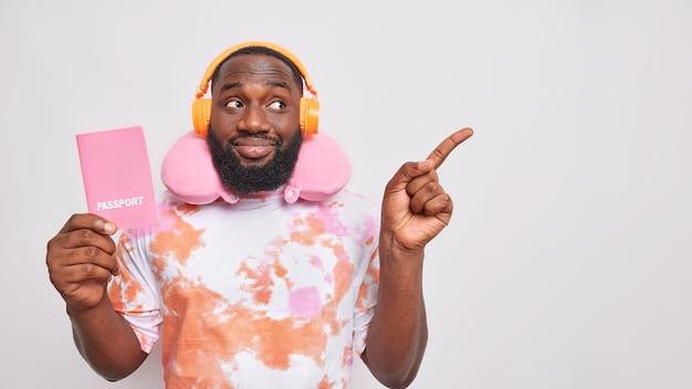 Горизонтальный снимок красивого бородатого мужчины со смуглой кожей путешествует в транспорте, держит в руках паспорт, использует подушку для шеи, слушает музыку через беспроводные наушники, указывает на изолированное над белой стеной