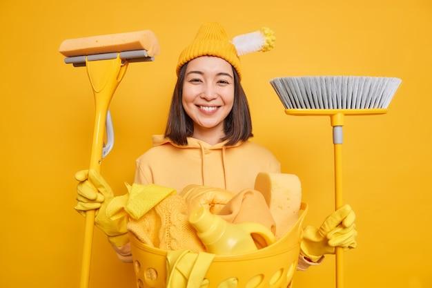 Горизонтальный снимок счастливой азиатской девушки, помогающей маме по дому, держит швабру, а метла имеет радостное выражение, носит шляпу, толстовку, защитные резиновые перчатки, изолированные на желтом фоне. домашняя работа
