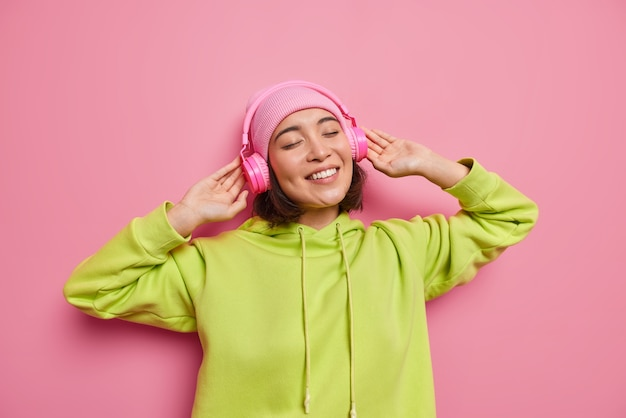 행복한 아시아 10대 소녀가 새 헤드폰으로 좋은 음질을 즐기는 수평 사진은 좋아하는 음악을 듣고 만족스러운 미소로 눈을 감고 분홍색 벽에 격리된 후드티와 모자를 광범위하게 착용합니다