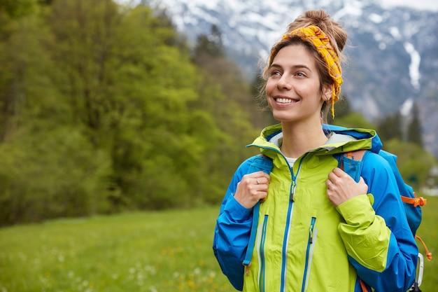 幸せなのんきな若い女性の水平方向のショットは、山の風景に対して外を散歩し、牧草地で自由な時間を過ごすことを楽しんでいます