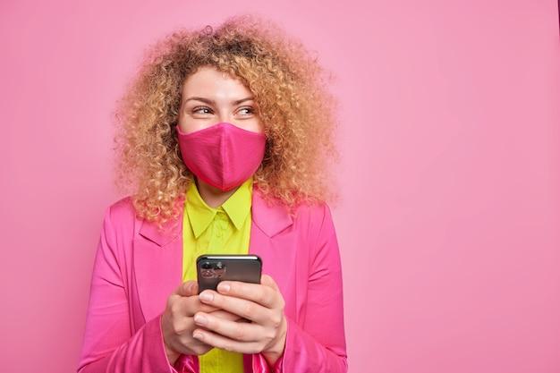幸せな巻き毛の若い女性が保護マスクを着ている横方向のショットは、保護フェイスマスクを慎重に着て目をそらし、コピースペースのあるピンクの壁にフォーマルな服のポーズをしている