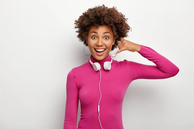 행복 한 어두운 피부 여자의 가로 샷 전화 제스처를 만들고, 긍정적으로 보이고, 목에 헤드폰을 착용하고, 흰색 배경에 대해 포즈를 취하고, 기쁘게 생각합니다. 신체 언어