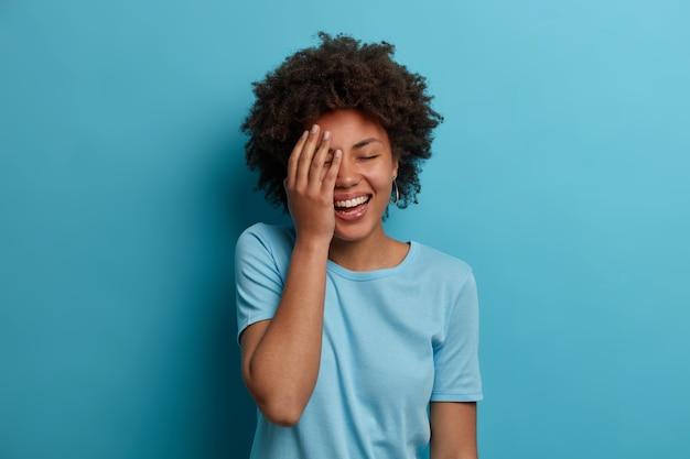 Горизонтальный снимок счастливой темнокожей женщины делает лицо ладонью, позитивно хихикает, держит глаза закрытыми, у нее хорошее настроение, носит синюю футболку, позирует в помещении, слышит потрясающую информацию, реагирует на удачную прекрасную ситуацию