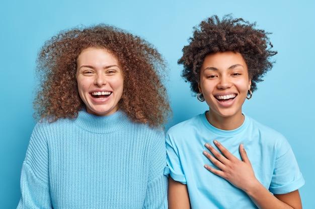 Горизонтальный снимок счастливых разноплановых женщин, которые положительно хихикают, имеют веселые выражения лиц, стоят близко друг к другу, выражают положительные эмоции, имеют дружеские отношения, изолированные на синей стене