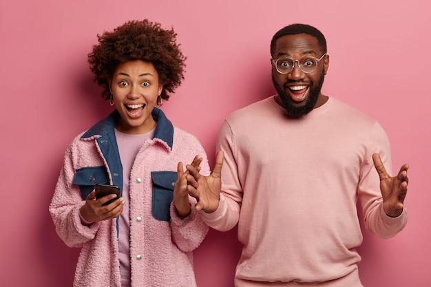 幸せな民族の女性と男性の水平方向のショットは、手と笑顔でジェスチャー、面白いと非常に面白い何かを説明しようとします