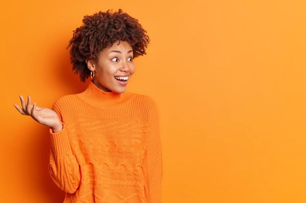 Горизонтальный снимок счастливой возбужденной женщины, поднимающей ладонь, замечающей что-то неожиданное, и удивительной улыбки, положительно одетой в повседневный джемпер, изолированного над ярко-оранжевой стеной