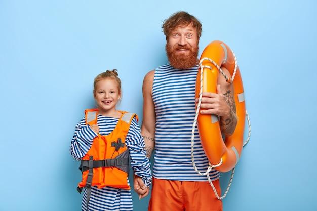 Горизонтальный снимок счастливых отца и ребенка в защитных спасательных жилетах, которые несут жизнь, вместе проводят летние каникулы, учатся плаванию, выражают хорошие эмоции