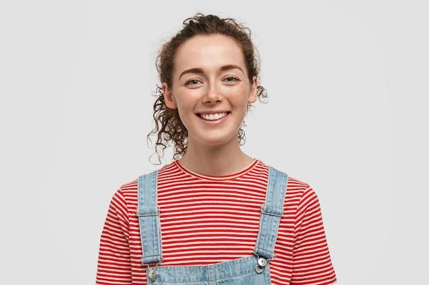 곱슬 머리, 즐거운 미소를 가진 행복한 주근깨가있는 여자 성인의 가로 샷은 행복하게 카메라를 찾습니다