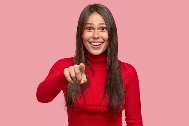 Горизонтальный снимок счастливого фрилансера, замечающего на расстоянии забавную сцену, указывает указательным пальцем прямо на камеру
