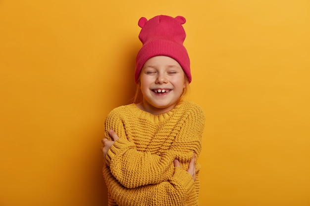 Горизонтальный снимок счастливой маленькой девочки, которая обнимает себя, чувствует уют, носит розовую шляпу и вязаный свитер, пребывая в приподнятом настроении, изолирована над желтой стеной. дети, чувство собственного достоинства