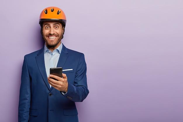 幸せなプロのエンジニアの水平方向のショットは、フォーマルなスーツと保護用のオレンジ色のヘッドギアを着用し、建設現場でオンラインで作業を制御するためにスマートフォンを使用しています