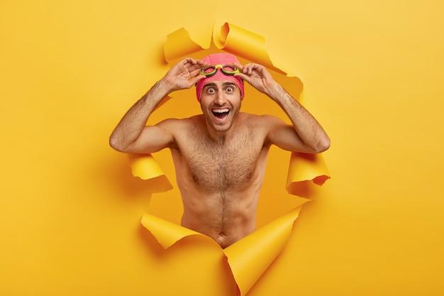행복 shirtless 남자의 수평 샷 수영 고글을 조정
