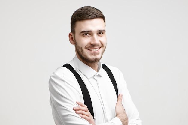 自信を持って笑顔、腕を組んで、自信、成功、決意を表現する彼の外観と姿勢で、剛毛とスタイリッシュなヘアカットで幸せな成功した若い起業家の水平方向のショット