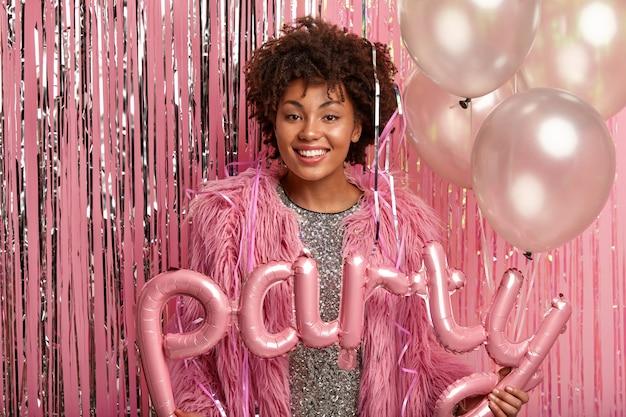 행복 한 여자의 가로 샷 특별한 날, 생일 또는 졸업을 기념하고, 공기 풍선을 보유하고, 세련된 옷을 입고, 반짝이는 분홍색 벽에 모델을 착용합니다. 휴일 개념