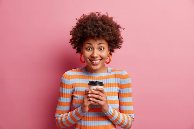 Горизонтальный снимок счастливой женщины, держащей бумажный стаканчик с кофе обеими руками, улыбается и выглядит удивительно в повседневном полосатом джемпере, изолированном над розовой стеной.